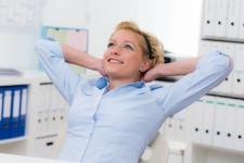 Mitarbeiterin im Büro denkt zufrieden an gelungene Arbeit